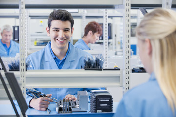 Portrait of smiling technician assembling circuit board in manufacturing plant