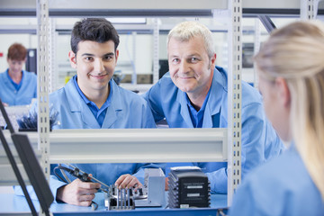 Portrait of smiling supervisor and technician assembling circuit board in manufacturing plant