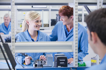Smiling supervisor and technician assembling circuit board in manufacturing plant