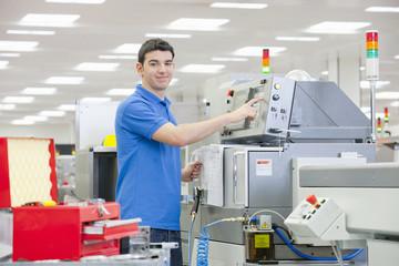 Portrait of smiling technician using machine in manufacturing plant