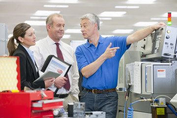 Engineer explaining machine to business people in manufacturing plant