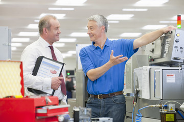 Engineer explaining machine to businessman in manufacturing plant
