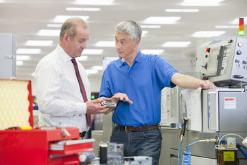 Engineer explaining machine part to businessman in manufacturing plant
