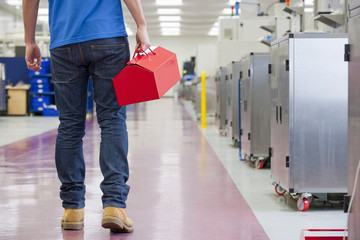 Repairman holding toolbox in aisle of manufacturing plant