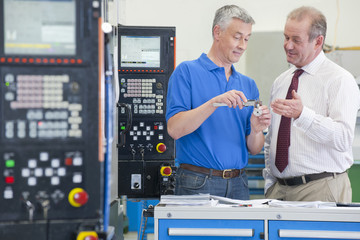 Businessman and engineer discussing machine parts in manufacturing plant