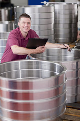 Portrait of smiling technician checking steel roller bearing inventory in warehouse