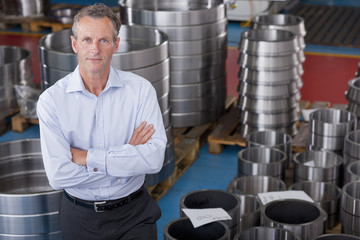 Portrait of serious Businessman standing among steel roller bearings in manufacturing plant