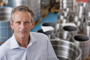 Close up portrait of confident businessman among steel roller bearings in manufacturing plant