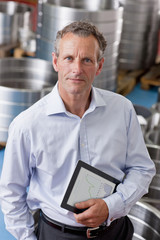 Portrait of confident businessman holding digital tablet among steel roller bearings in manufacturing plant