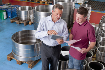 Businessman and technician with digital tablet and paperwork in steel roller bearing manufacturing plant