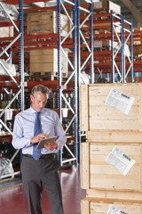 Businessman using digital tablet next to crates in warehouse