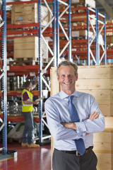 Portrait of smiling businessman with arms crossed in front of crates in warehouse