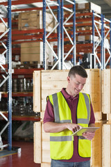 Smiling worker in reflector-vest using digital tablet in front of crates in warehouse