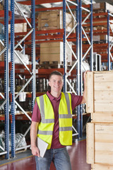 Portrait of confident worker in reflector-vest leaning on crates in warehouse