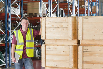 Portrait of smiling worker in reflector-vest holding digital tablet and leaning on crates in warehouse