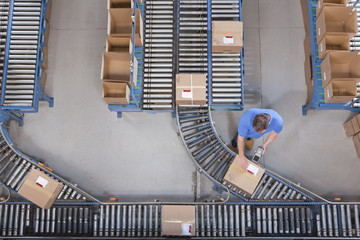 Worker with bar code reader scanning box on conveyor belt in distribution warehouse