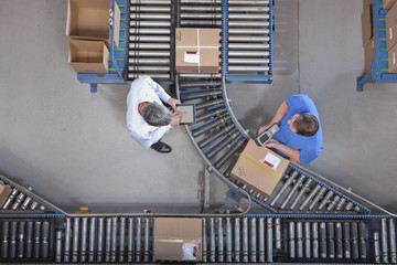 Businessman with digital tablet and worker packing box at conveyor belt in distribution warehouse