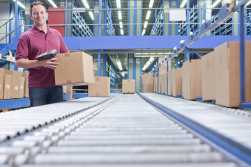 Portrait of smiling worker with bar code reader and box at conveyor belt in distribution warehouse