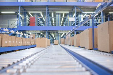 Boxes on conveyor belts in distribution warehouse