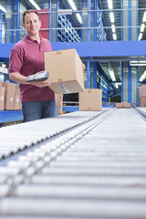 Portrait of smiling worker holding bar code reader and box at conveyor belt in distribution warehouse