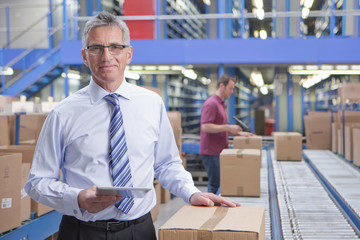 Portrait of smiling businessman holding digital tablet at conveyor belt in distribution warehouse