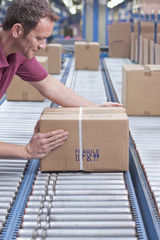 Worker packing box on conveyor belt in distribution warehouse