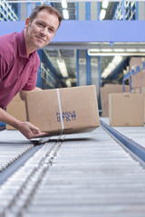 Portrait of smiling man packing box on conveyor belt in distribution warehouse