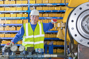 Portrait of smiling engineer leaning on machinery in factory