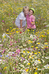 Portrait of smiling grandmother and granddaughter standing among wildflowers in sunny meadow