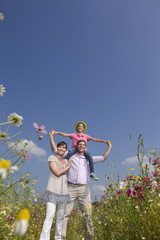 Portrait of smiling family among wildflowers in sunny meadow