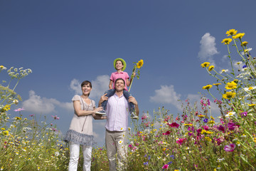 Portrait of happy family among wildflowers in sunny meadow