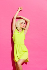Hot blond woman lean on the pink wall