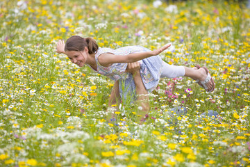 Father holding flying girl among wildflowers in sunny meadow