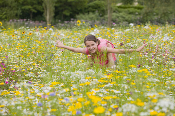 Father holding flying among wildflowers in sunny meadow