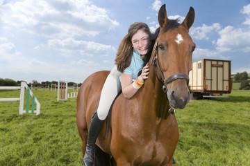 Portrait of smiling girl on horseback in field