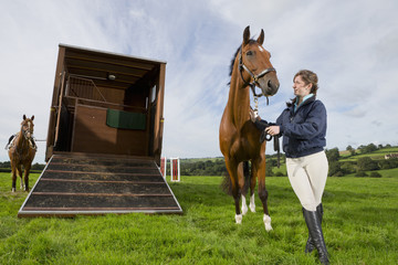 Girl with horse next to ramp of horse trailer