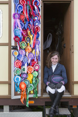 Portrait of smiling girl in equestrian uniform sitting in doorway of trailer with rosettes covering door