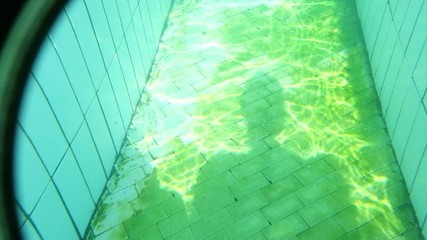 Sun flares on the bottom of swimming pool underwater footage