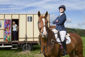 Portrait of confident girl in equestrian uniform on horseback near trailer