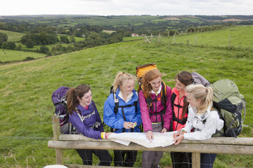 Girls with backpacks looking down at compass and map against fence in field