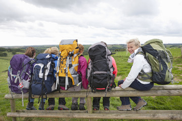 Girls with backpacks sitting in a row on fence in field