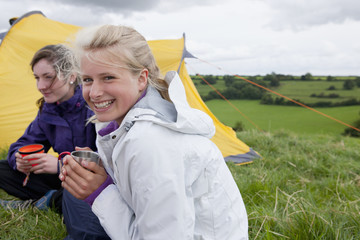 Portrait of smiling girls drinking tea next to tent