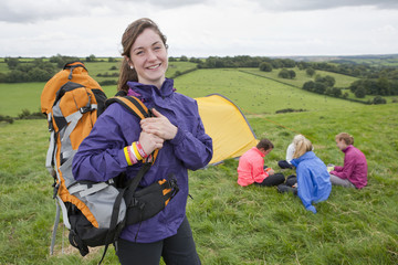 Portrait of smiling girl with backpack near friends and tent in rural field
