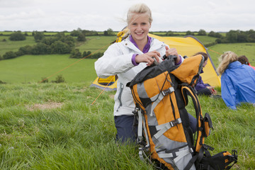 Portrait of smiling girl packing backpack near tent in rural field