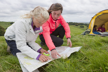Girls looking down at compass and map in rural field