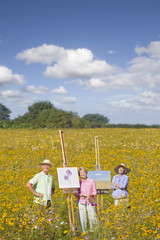 Portrait of smiling people painting on easels among wildflowers in sunny meadow
