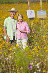 Portrait of smiling couple painting with easels among wildflowers in sunny meadow