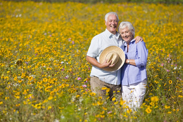 Portrait of smiling couple standing among wildflowers in sunny meadow