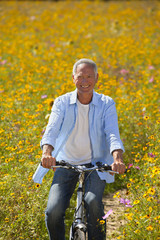 Portrait of smiling man riding bicycle among wildflowers in sunny meadow