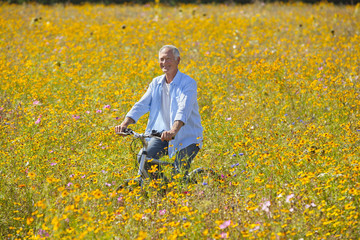 Smiling man riding bicycle among wildflowers in sunny meadow